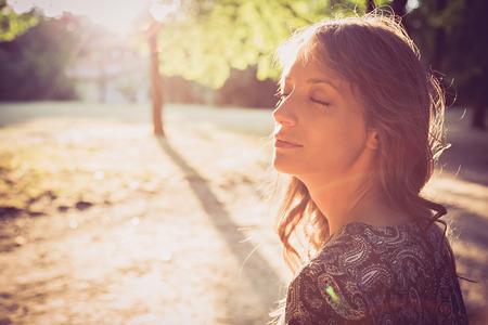 Retrato de una niña en el parque con los ojos cerrados. el reflejo del sol Foto de archivo