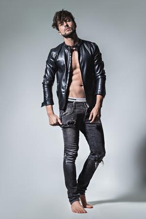 actitud: El hombre con la actitud que presenta en chaqueta de cuero y pantalones vaqueros. Estudio