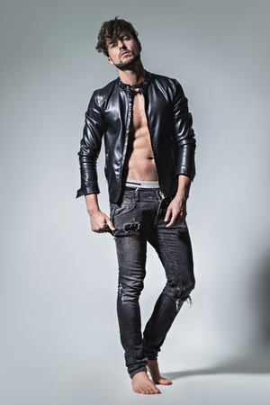Man with attitude posing in leather jacket and jeans. Studio
