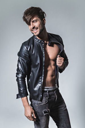 casual men: Man smiling and posing in leather jacket and jeansStudio