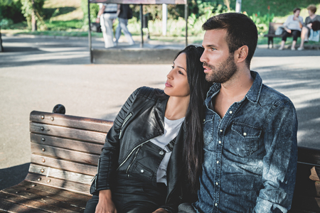 romantic couple: Couple sitting on a park bench enjoying the view on a suuny day