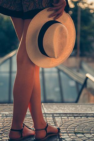 manos y pies: Chica de pie y sosteniendo su sombrero. La puesta del sol
