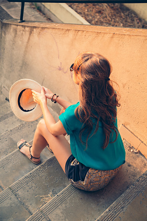 Girl sitting on the stairs and holding her hat