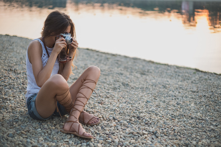 camera girl: Girl sitting on the beach and photographing. Sunset