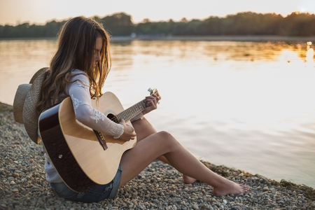 Girl playing guitar while sitting on the beach. Sunset