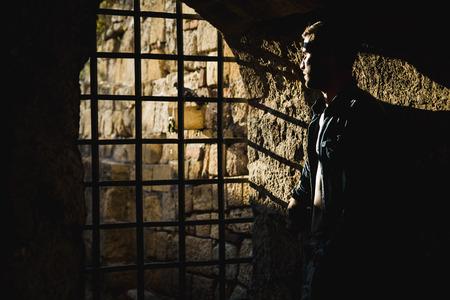 shadow man: Man looking at the sun trough cell bars