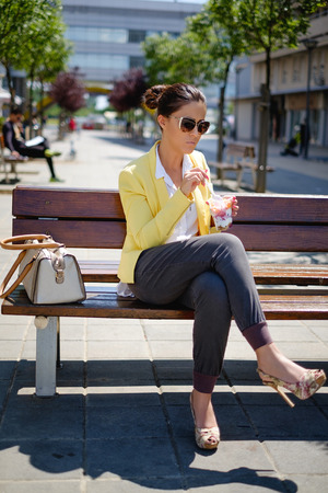 Business woman sitting on the bench and eating healthy food
