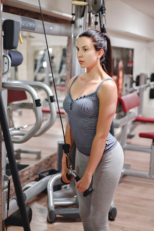 triceps: Girl doing triceps pushdown in the gym