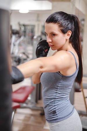 punching: Girl focus on punching bag  in the gym. Vertical