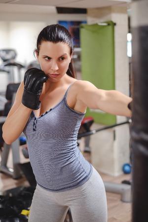 tough girl: Tough girl punching the bag in the gym