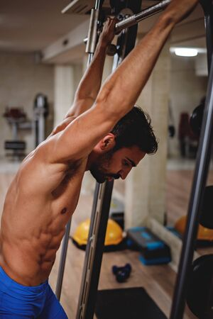 low energy: Tired man hanging from the bar in the gym