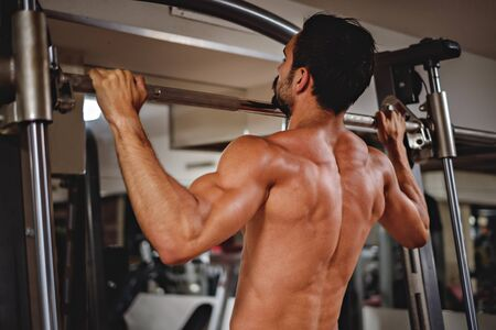 strong chin: Man doing pull ups on the bar in the gym