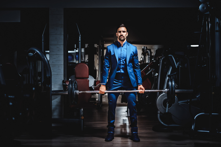 heavy weight: Man in suit lifting heavy weight in the gym