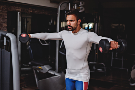 raises: Man doing shoulder lateral raises in the gym Stock Photo