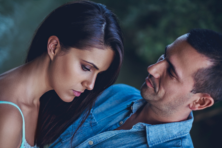 Troubled couple hugging sadly and looking down Stock Photo