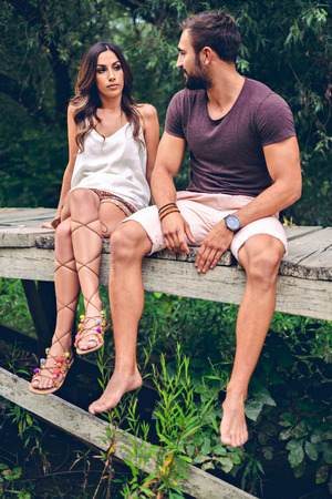 muscled: Girl looks suspicious at her boyfriend while sitting at the pier Stock Photo