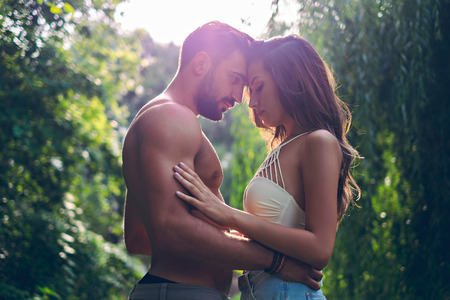 sensually: Couple holding each other in park sensually with sun behind them