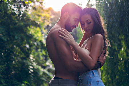 Man cuddle with his girlfriend in the park with sun behind them