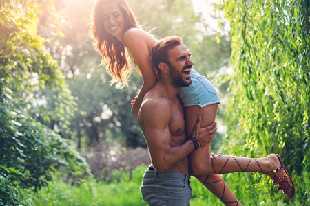 lifting: Man lifting his girl up and they are both laughing