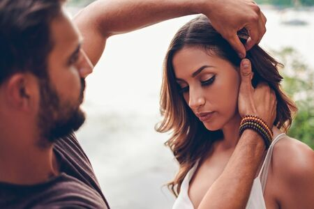 belle brune: Man is fixing girls hair by the water Banque d'images