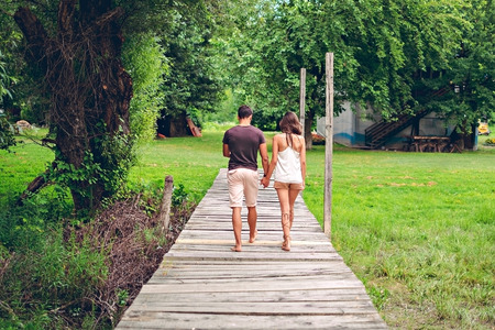 sandal tree: Couple holding hands and walking on the pier in to the forest. Horizontal