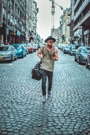 mobile app: Hipster walking on the street carrying bag and looking at phone