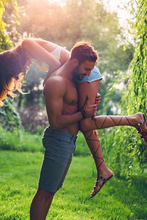 pareja apasionada: Elevación del hombre a su novia mientras ella grita. La puesta del sol Foto de archivo