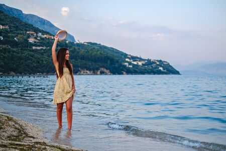 Girl waving with her hat and walking on the beach