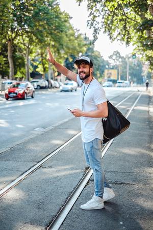 Glücklicher Mann auf der Straße ein Taxi zu stoppen Standard-Bild - 63275979