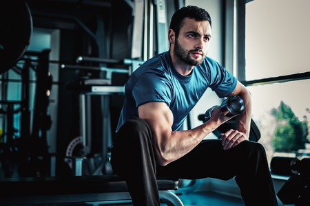 Concentrated man workout biceps on a bench in a gym