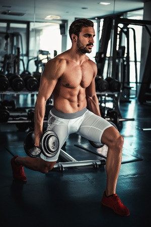 lunges: Shirtless man training legs in the gym