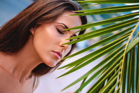 Girl with closed eyes behind the palm leaves. Summertime Imagens