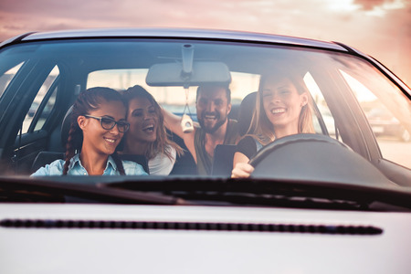 Group of friends having fun in the car. Sunset Stock Photo