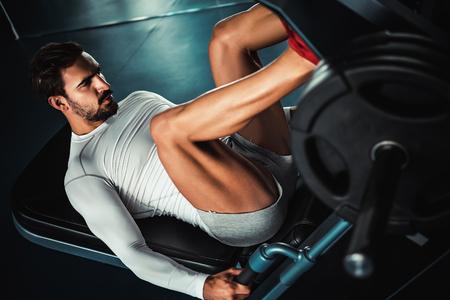 Fit man training legs on leg press machine in the gym