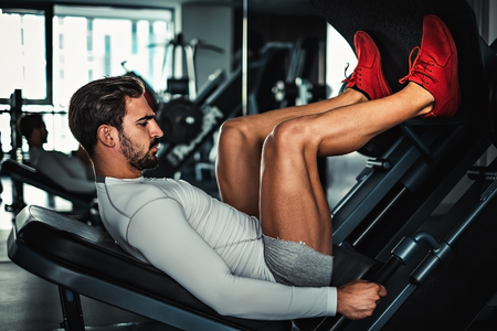 Man focused on training legs on the machine in the gym