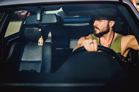 dia soleado: Hipster musculoso hombre conducir un automóvil en un día soleado Foto de archivo
