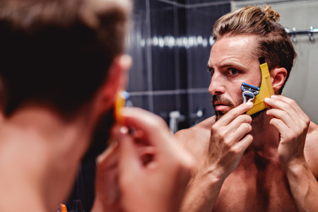Hipster man shaving his beard in the bathroom Stockfoto