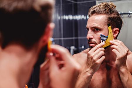 Hipster man shaving his beard in the bathroom Foto de archivo