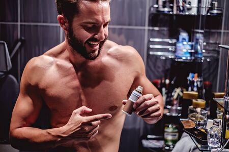 aftershave: Hipster man showing bottle in the bathroom and smiling