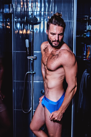 Man entering bathtub for a shower and a scrub Stock Photo