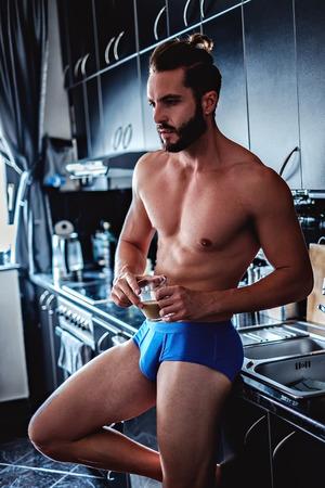 ropa interior: Hombre apto en ropa interior bebiendo café en la cocina mientras se inclina sobre el lavabo