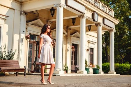 Ragazza in piedi davanti alla vecchia stazione ferroviaria. Caldo giorno d'estate