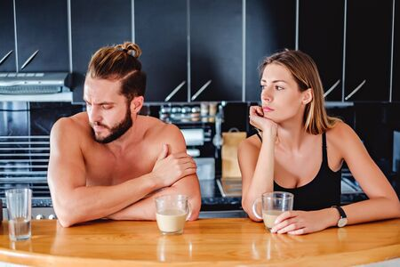 not talking: Couple not talking to each other while sitting in the kitchen