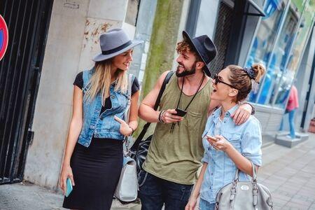 sidewalk talk: Three friend walking and  talking on the sidewalk Stock Photo