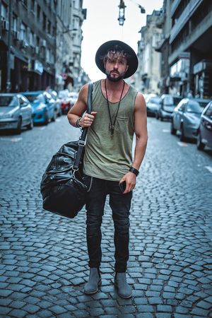 young male: Hipster standing in the street carrying his bag and phone