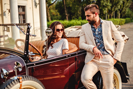 Man hitting on a woman in a classic convertible. Summer day