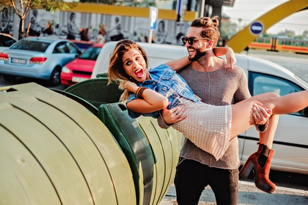 trash the dress: Man pretending to throw girl in the garbage