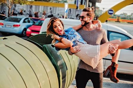 joking: Man pretending to throw girl in the garbage