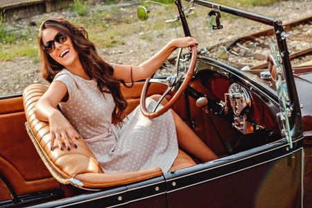 Muchacha de risa mientras se conduce un coche viejo clásico y mirando detrás de ella