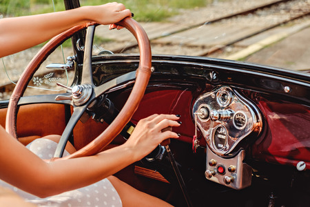 drive car: Female hands on classic car steering wheel and shift